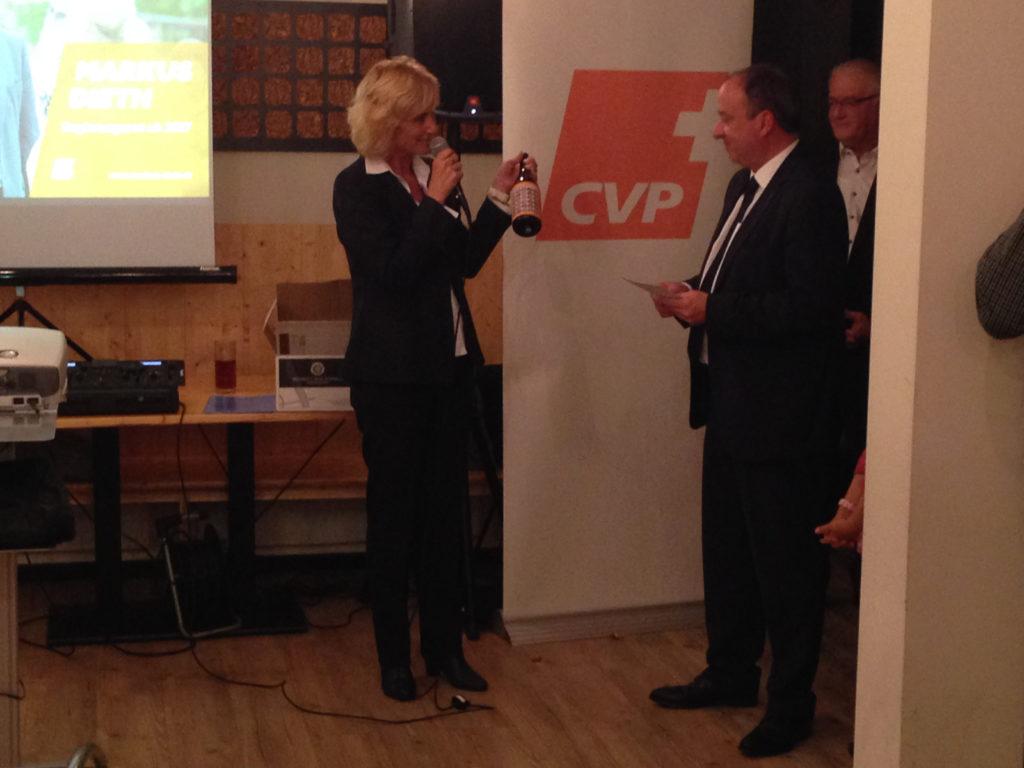 Susanne Voser überreicht Markus Dieth eine Flasche Wein mit den Gesichtern sämtlicher Kandidatinnen und Kandidaten der CVP des Bezirks Baden.